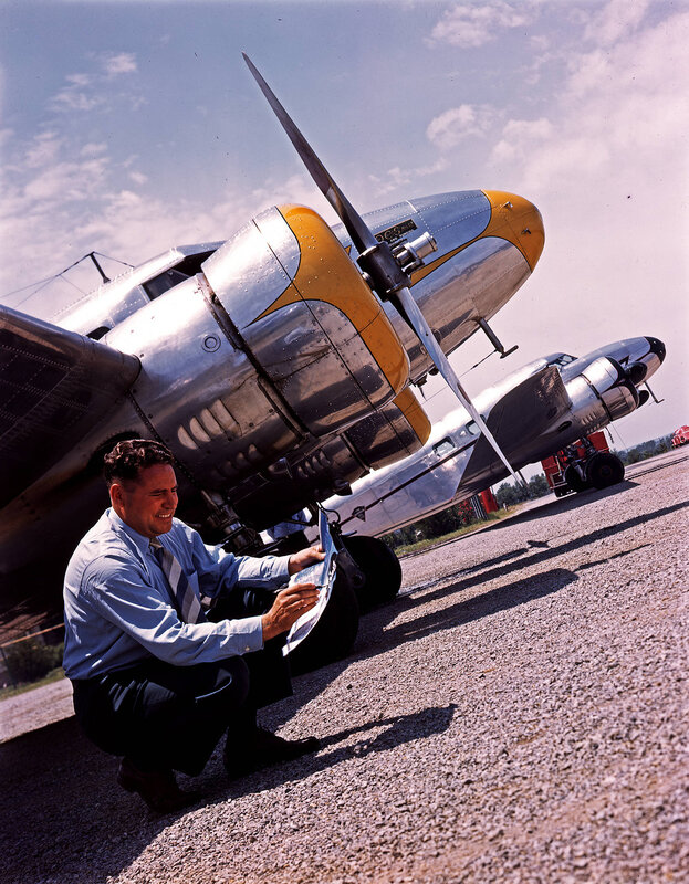 A man marking a document while in front of two Lockheed Model 12A Electra Junior aircraft, belonging to the Oil Country Services Manufacturing Company and the Superior Oil Company, at William P. Hobby Airport in Houston, Texas. March 1940