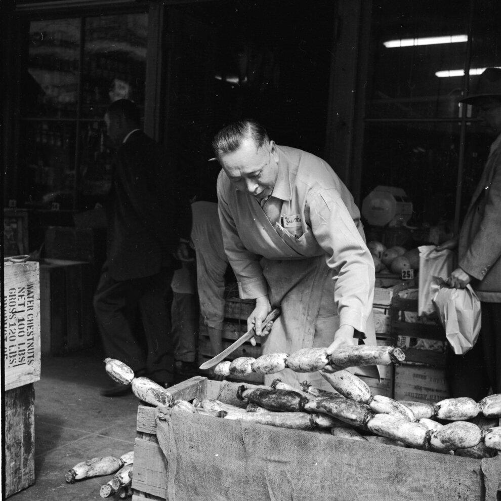 Продавец отрезает кусок корня лотоса для клиента