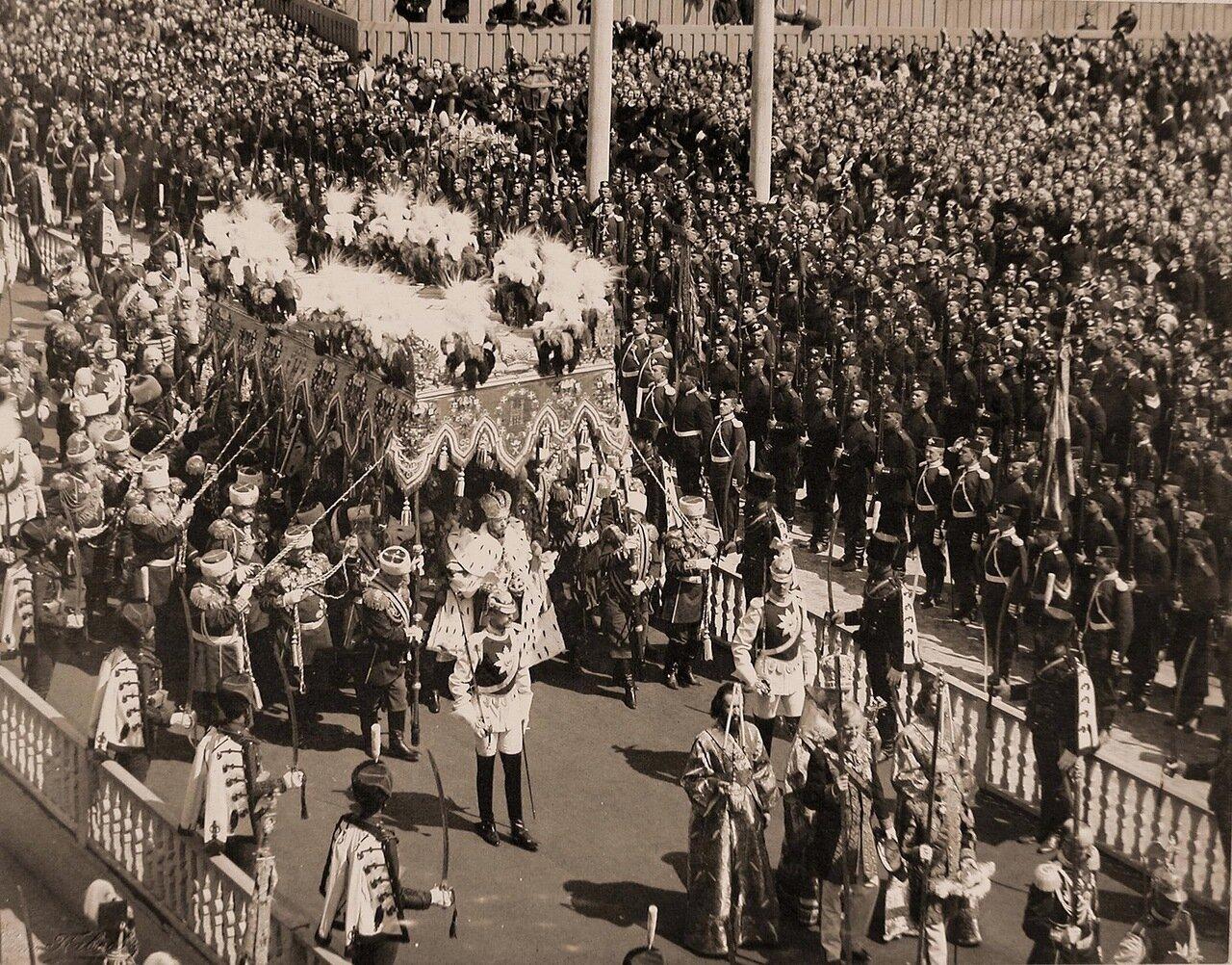 Торжественное шествие императора Николая II (под балдахином) в сопровождении свиты по окончании церемонии коронации в Успенском соборе Кремля; справа (в нижнем углу снимка) - церемониймейстеры (с жезлами)