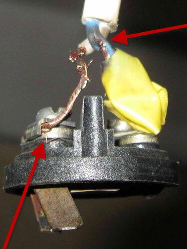 Фото 11. Местные последствия короткого замыкания (на них указывает верхняя тёмно-красная стрелка). Обратите внимание на отдельные необжатые «волоски» провода на левом контакте (нижняя стрелка).
