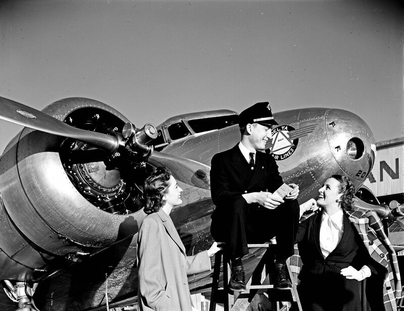 A Delta Air Lines station agent, with two models, in front of a Lockheed Model 10B Electra, owned by Delta Air Lines, at Dallas Love Field Airport. March 1940
