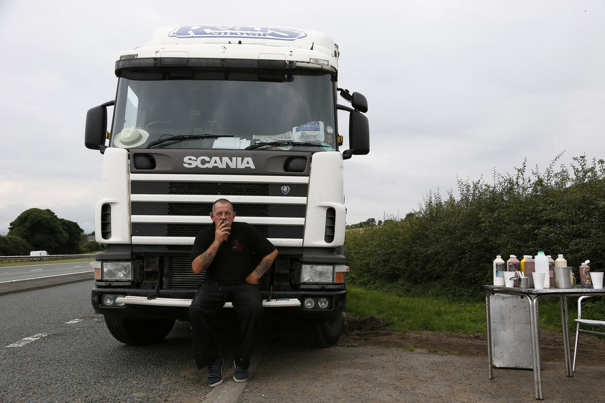 Kevan Brown, a 53 year-old truck driver, poses for a photograph in front of his vehicle, along the A69 near Newton