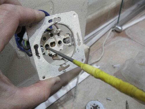 Фото 26. Зачистка контактов розетки с помощью круглого надфиля. Выполняется под напряжением. Ручка надфиля обмотана изоляционной лентой.