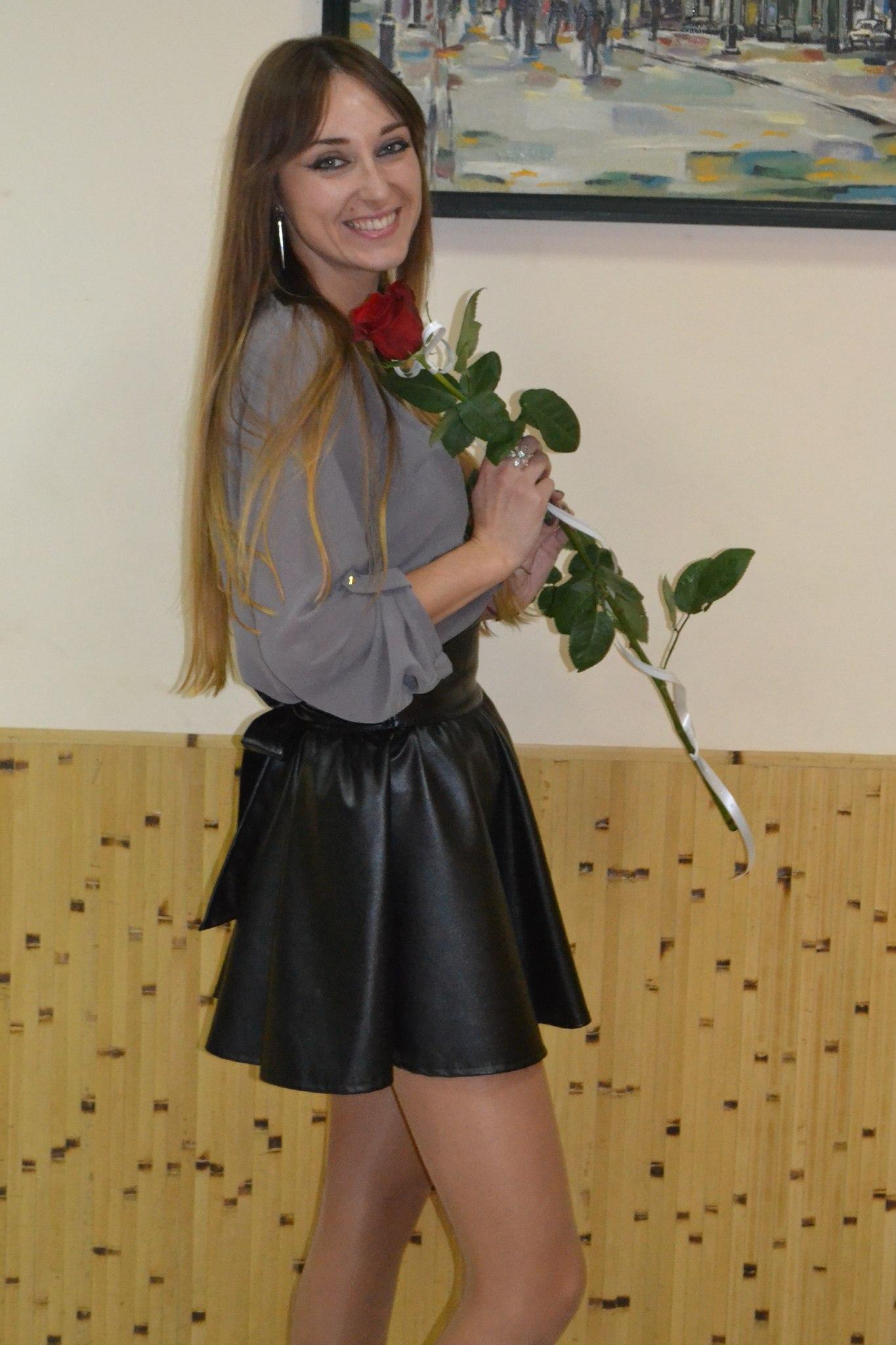 Привлекательная девчонка в кожаной юбке и серой рубашке