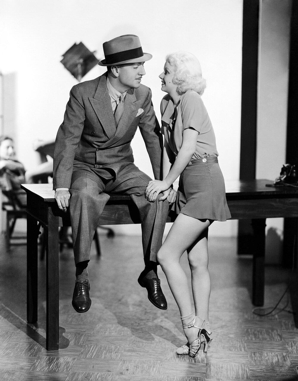 24th January 1935: Jean Harlow (1911-1937), wearing flared shorts and a blouse, with co-star William Powell (1892-1984) during the filming of the MGM musical comedy 'Reckless'. (Photo by Clarence Sinclair Bull)