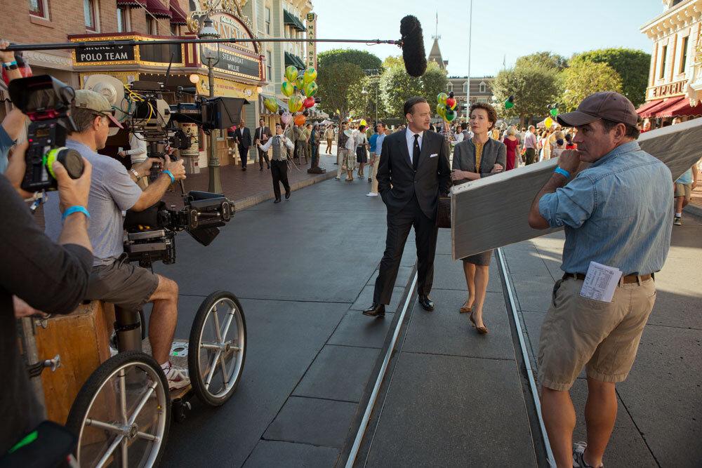 """SAVING MR. BANKS""Walt Disney (Tom Hanks), left center,  P.L. Travers (Emma Thompson), right center, and John Schwartzman during filming of Disney's ""Saving Mr. Banks"".Ph: François Duhamel©Disney Enterprises, Inc.  All Rights Reserved."