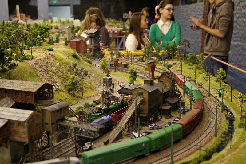 Гранд макет: место ночной спецоперации. Товарняк на железной дороге, заброшенный завод и посетители выставки для контраста в размере.
