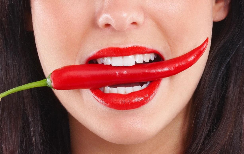 девушка с красным перцем во рту