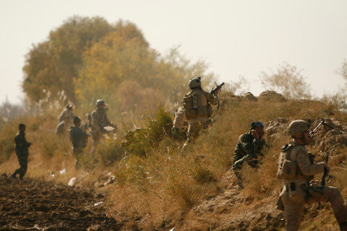 Afghan National Policemen and U.S. Special Forces engage insurgents on the far side of a canal while pulling security near the village of Hyderabad, Gereshk District, Helmand province Dec. 3. A combined force totaling more than 350 international troops em
