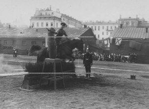 Демонстрация рубки чучела с одновременным преодолением барьера во время конных состязаний на плацу.
