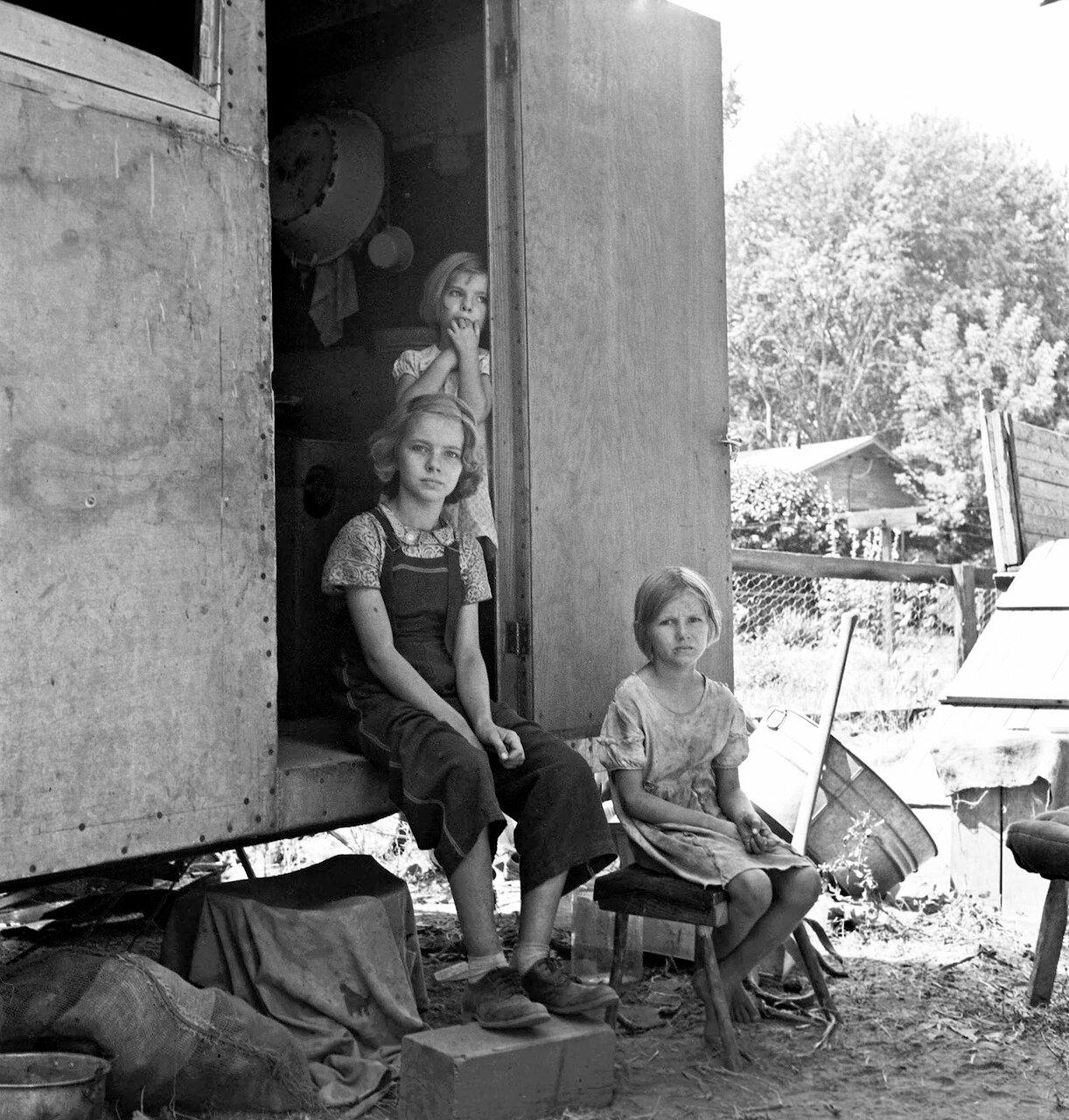 Старшая по возрасту девочка сидит в дверях дома-прицепа, следит за младшими. Якима, штат Вашингтон , 1939
