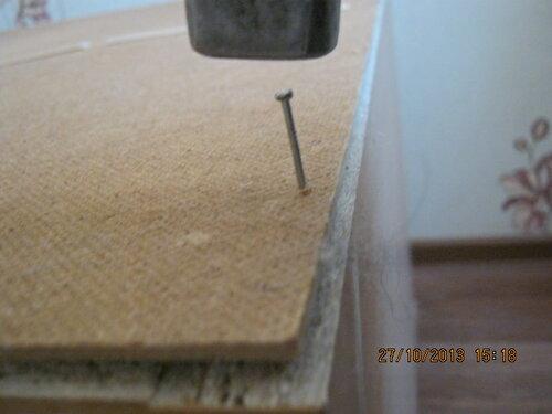 Тщательно отцентровал прямоугольник задней стенки и вихлястую коробку шкафа. Начинаю прибивать.