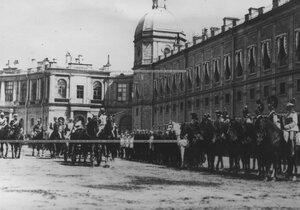 Члены императорской фамилии в коляске в сопровождении свиты объезжают выстроившиеся для парада подразделения полка.
