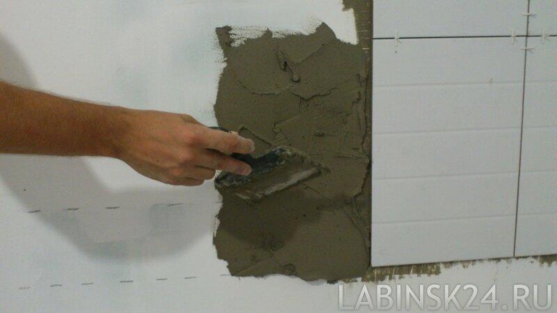 Наносим клей плоским шпанелем на стену