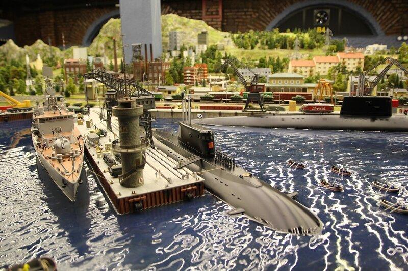 Гранд макет: пирс с маяком, пришвартованный к нему военный корабль и подводная лодка с построившимися на ней моряками