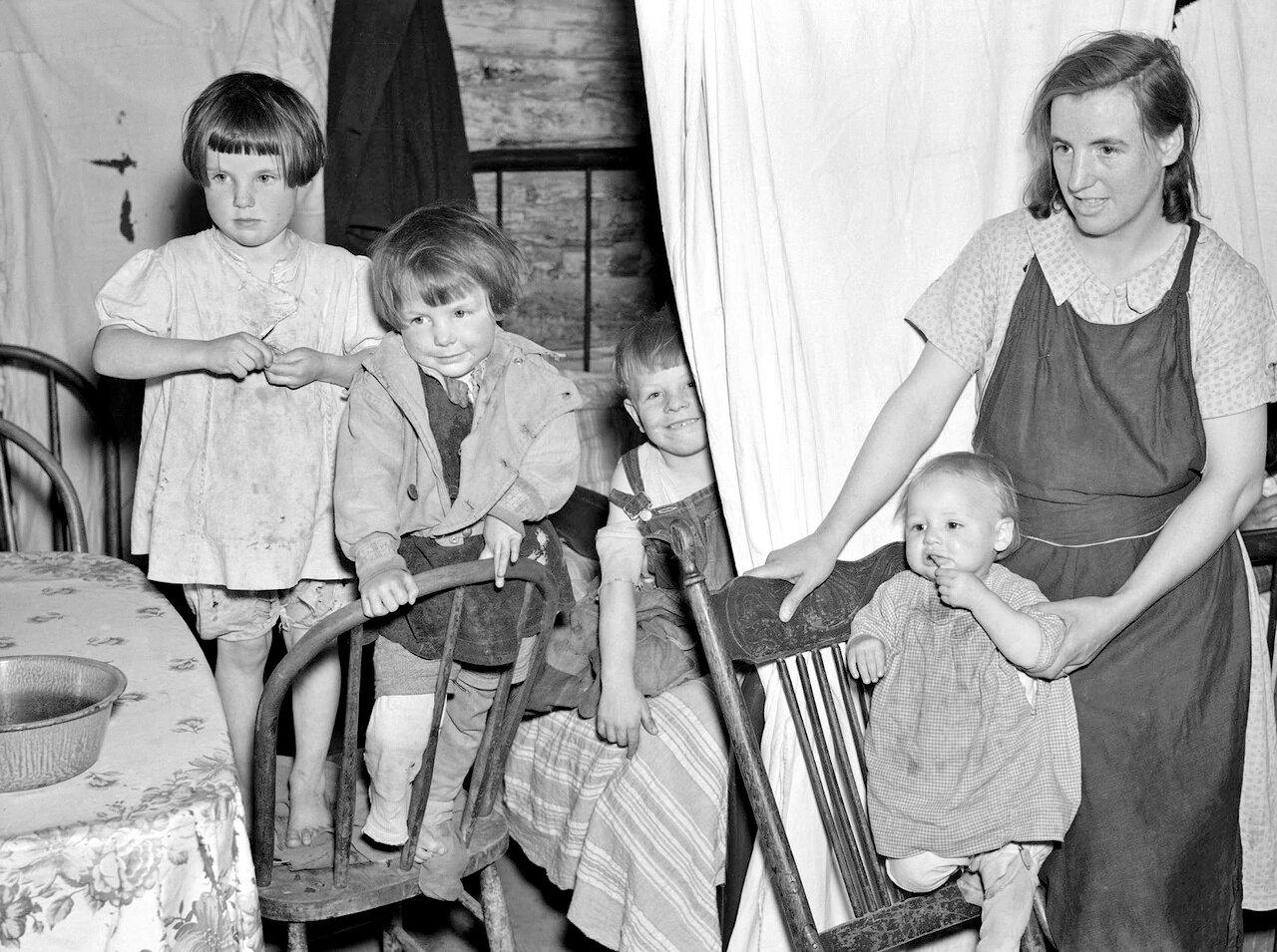 Дети дочери госпожи Бодрай в их лачуге возле Типлера, Висконсин. Занавеска отделяет переднюю часть их жидища от остального помещения, 1937