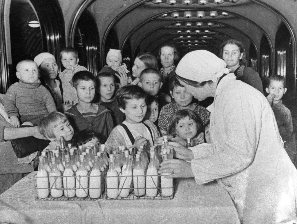 В московском метро, на станции «Маяковская», используемой как бомбоубежище, идет раздача молока детям. Январь 1942