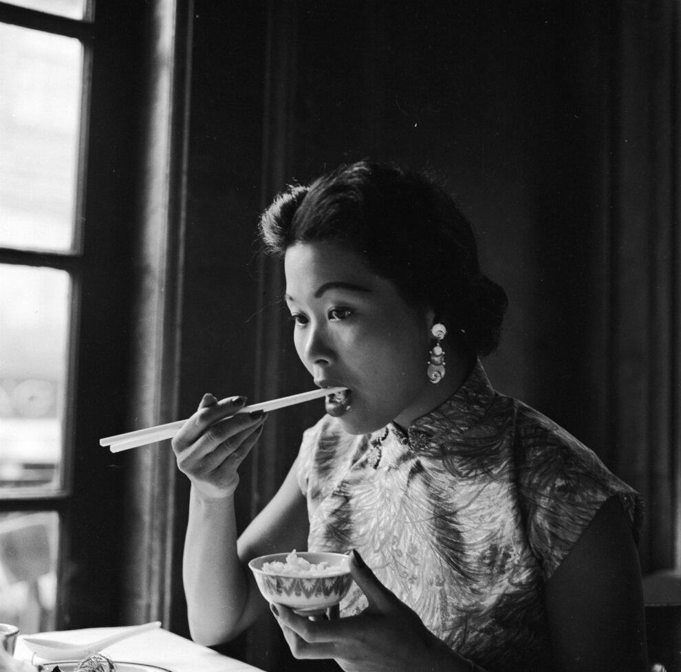 Женщина ест рис в ресторане