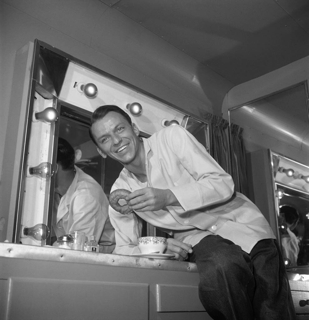 1950. Фрэнк Синатра поглощает пончик в своем трейлере в перерыве съемок