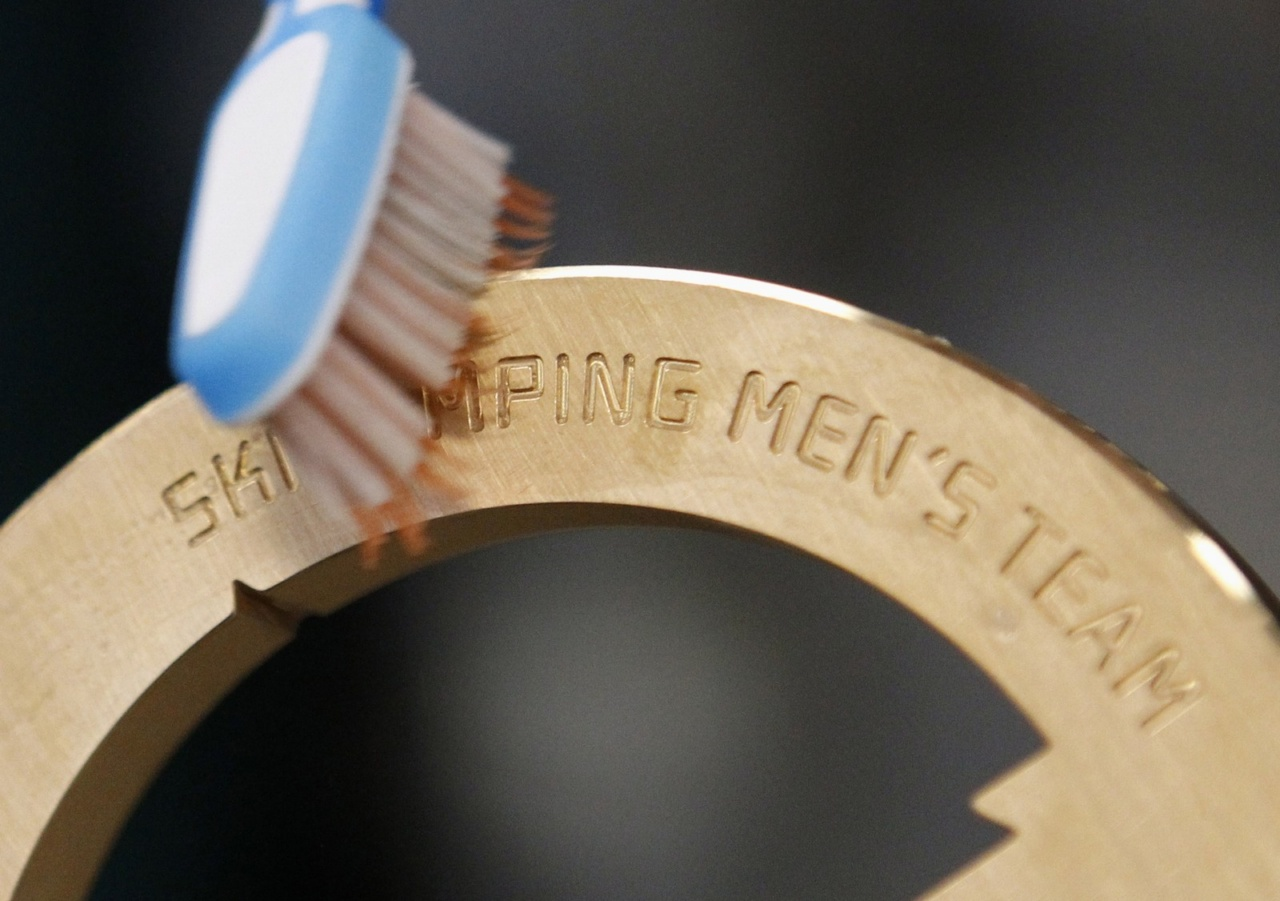 An employee uses a brush to clean a bronze medal manufactured for the 2014 Winter Olympic Games in Sochi, at the Adamas jewellery factory in Moscow