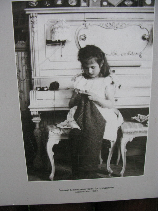 Велика княжна Анастасия что-то шьёт. Фото на стене монастыря.