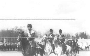 Император Николай II в сопровождении казаков направляется ко дворцу после окончания парада полка.