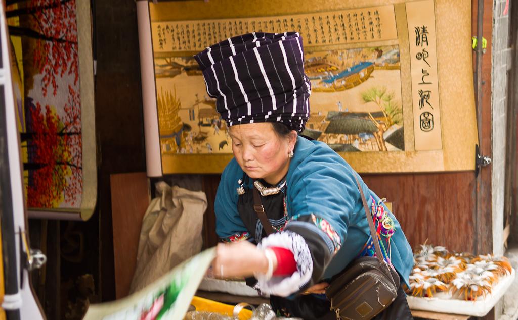 21. Продавец декоративных скатертей. Думаю, эта тётя также принадлежит народности мяо. Отзыв об экскурсии в Фэнхуан во время поездки из Чжанцзяцзе в Лунцзи. Приключения россиян в Китае.
