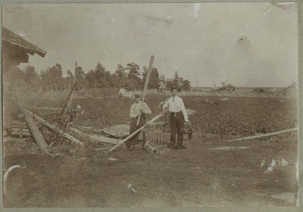 1900. Двое мужчин с веслами и деревянным ведром перед огородом
