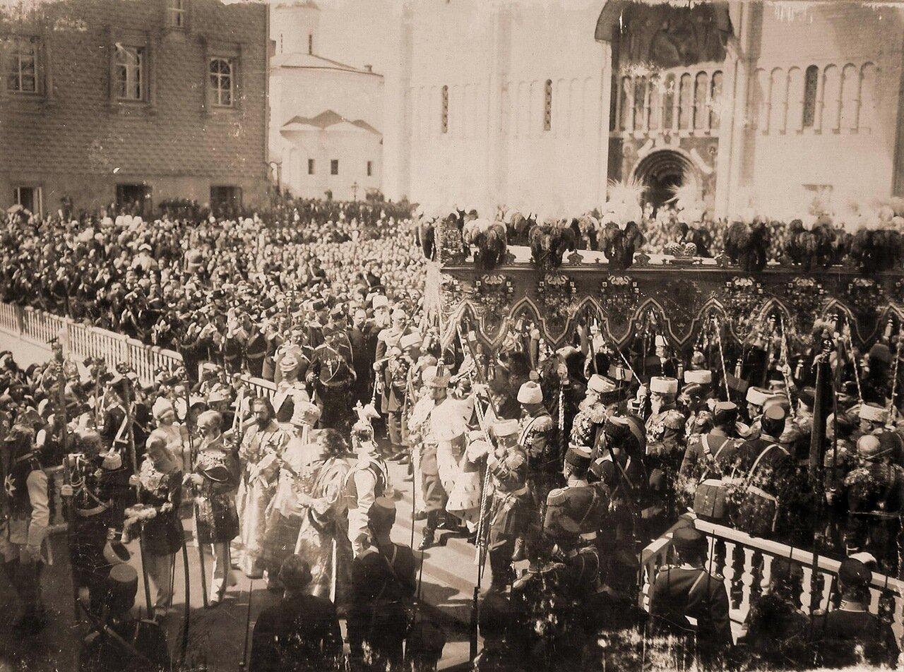 Император Николай II (под балдахином) в сопровождении свиты выходит из южных дверей Успенского собора на Соборную площадь Кремля по окончании церемонии торжественной коронации; перед императором - митрополит Санкт-Петербурга