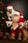 Portrait of happy Santa Claus sitting at his room at home with his woman helper near Christmas tree