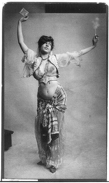 Woman in belly-dancing costume smoking and holding package of cigarettes 1900