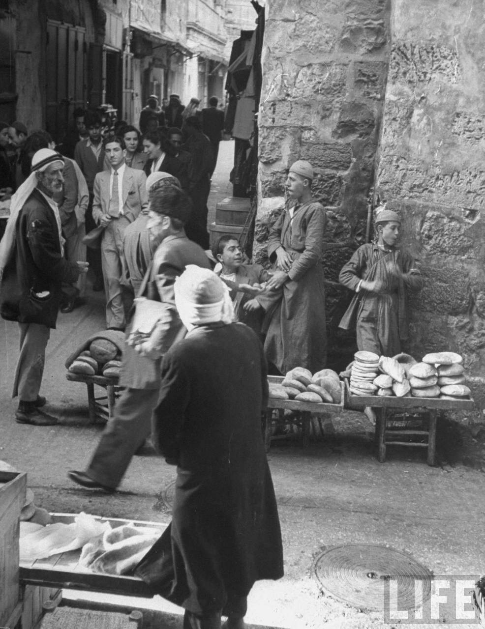 1949. Хлеб и мясо продаются на открытом воздухе на улице в старой части Иерусалима