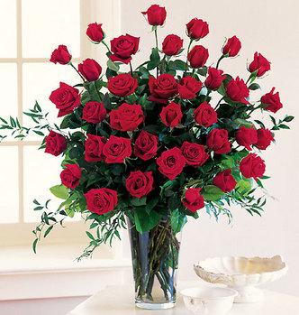 Букет красных роз стоит рядом с окном