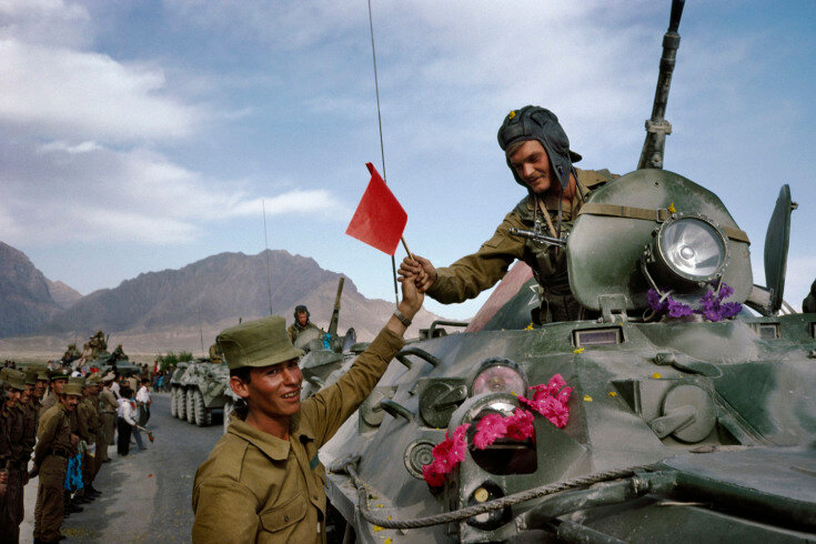 May, 1988. An Afghan army soldier hands a Soviet flag in solidarity  to a departing Soviet soldier on the first day of the Soviet army's withdrawal from Afghanistan.
