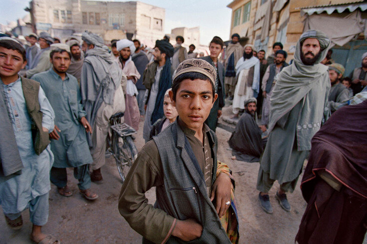 Sec3_13_173: Kandahar, 2001 Local residents and Taliban gaze at a group of foreign journalists crossing through a central market following ten days of US airstrikes on Kandahar city. After the 9-11 attacks, US Air Force planes attempted to destroy the Tal