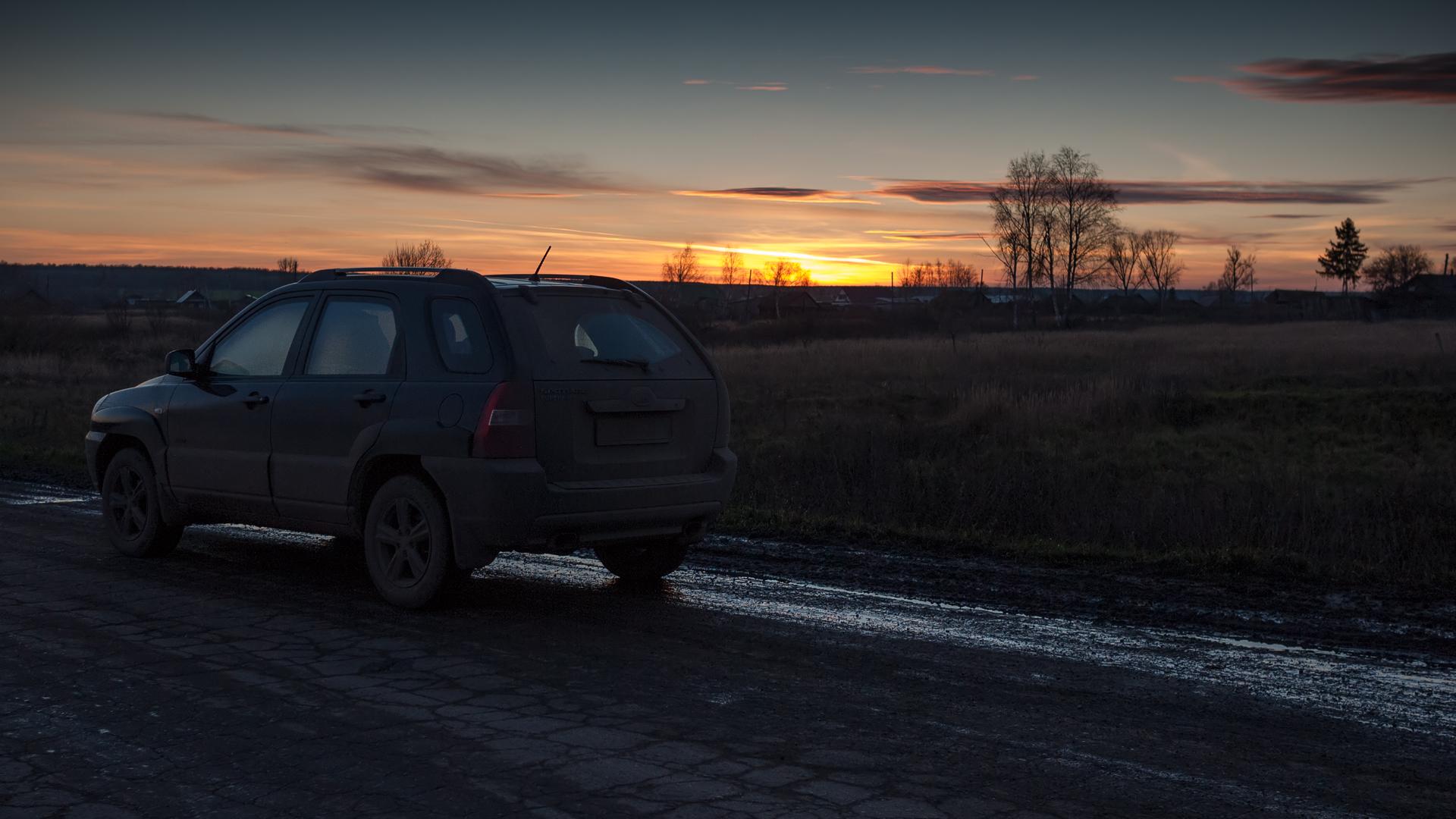 На закате. Дороги настолько грязные, что задняя дверь автомобиля покрыта сантиметровым слоем грязи.