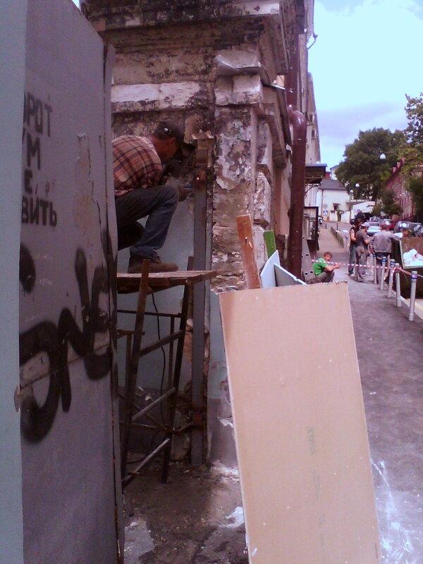 На белокаменных воротах срезаны металлические подставы и приваривается уголок. В белом камне вырублена штроба