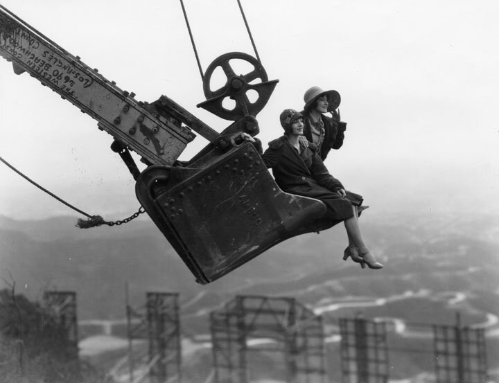 Two fashionably dressed women look out over Hollywoodland and its iconic sign from the vantage point of a raised steam shovel bucket, 1924
