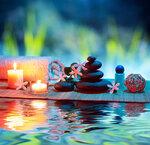 two candles and towels black stones and tiare on water