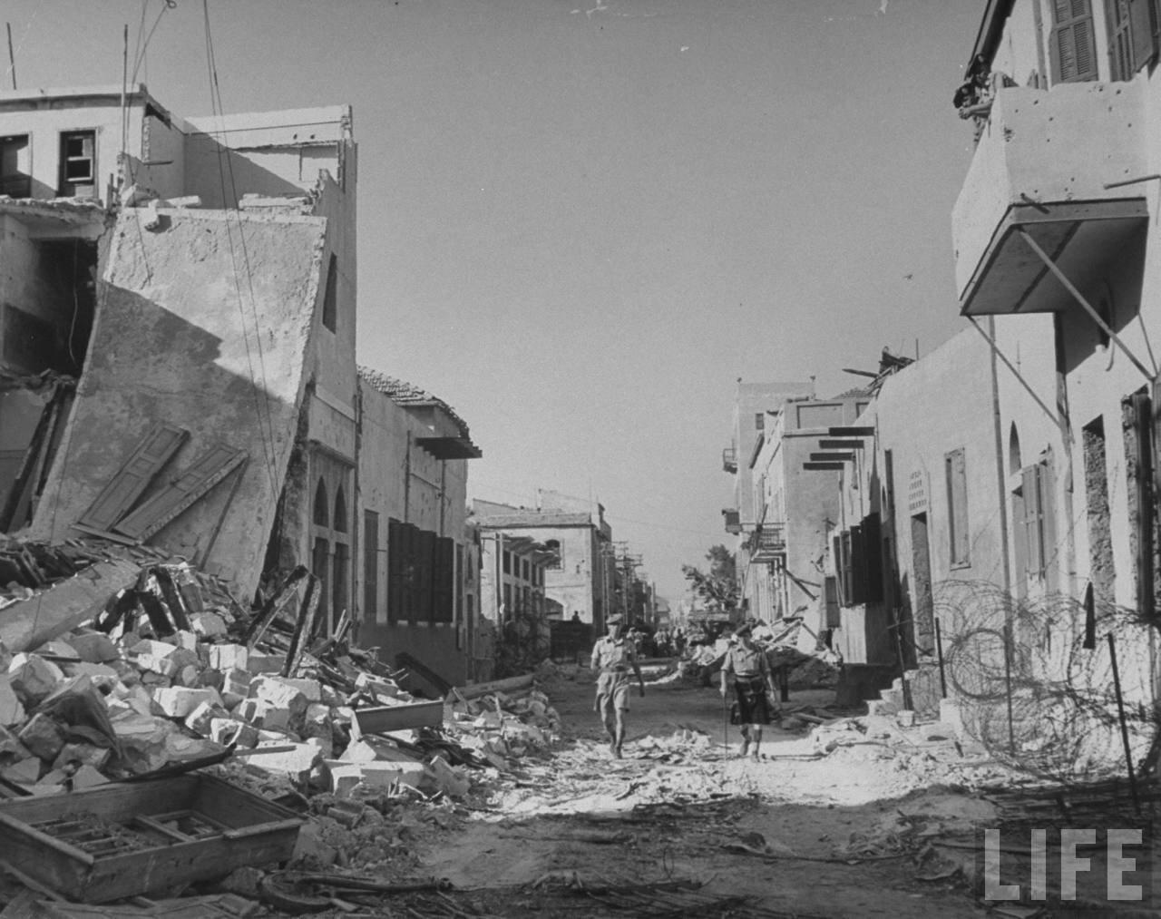 1948.Май. Два солдата идут среди развалин, точное местоположение неизвестно