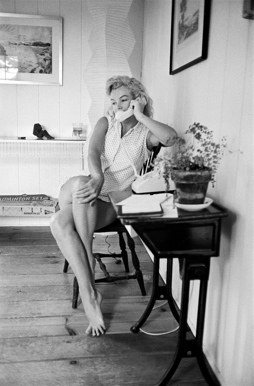 AMAGANSETT, NY - 1957: Marilyn Monroe sits with her legs crossed and her hand on one knee while talk