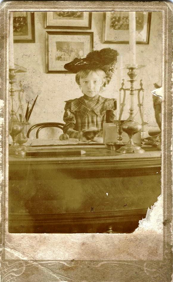 Девочка Гладышева Ольга Ивановна за письменным столом в кабинете. 1904