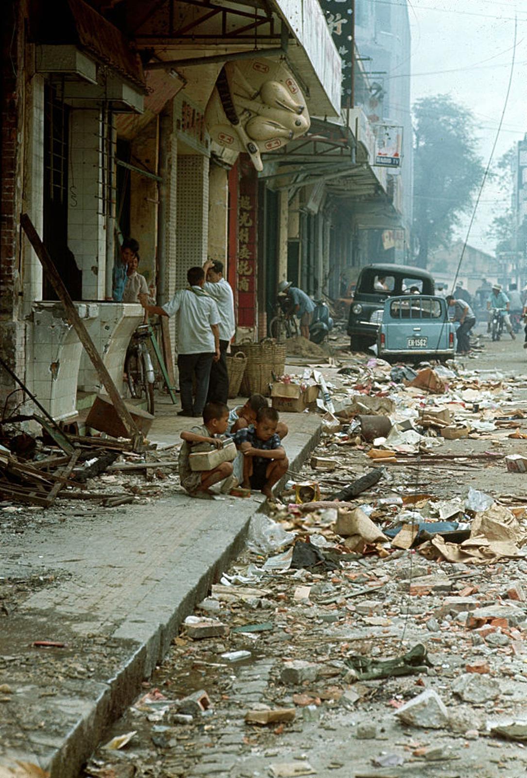 Район Тёлон после того, как большая часть боёв закончилась. Люди стоят под навесом здания, которое не было разрушено, а улица усыпана щебнем. 10 июня