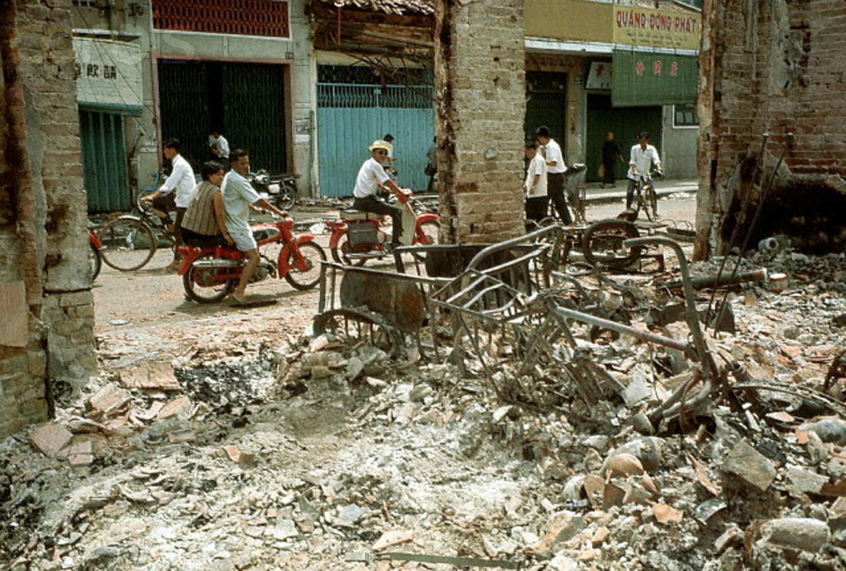 Район Тёлон после того, как большая часть боёв закончилась. Мотоциклисты проезжают мимо разрушенного здания. 10 июня