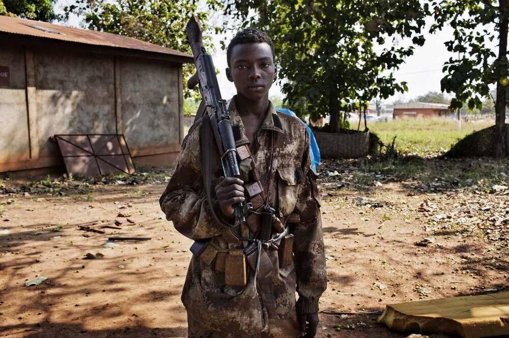 Мальчик-солдат из сил мусульманской Seleka позирует с оружием в городе Босангое