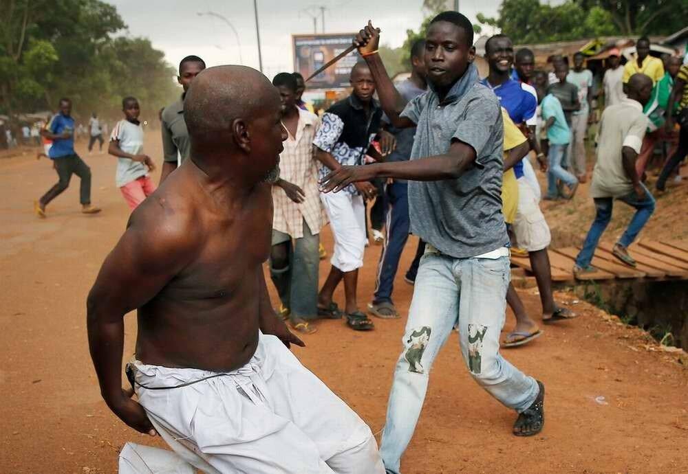 Негр-христианин преследует с ножом замеченного офицера мусульманской Seleka в штатской одежде возле аэропорта в Банги 9 декабря 2013 года