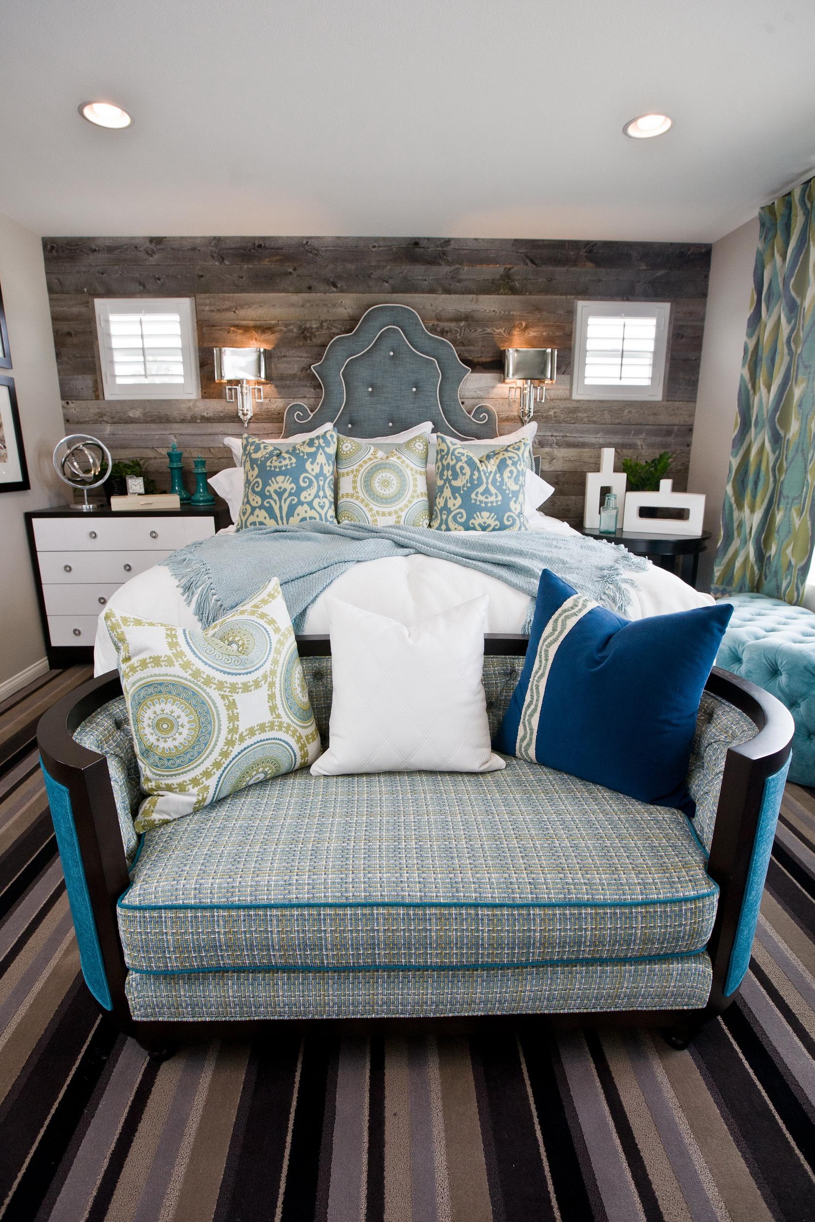 Спальня в синих. белых и зеленых тонах. Натуральная древесина на стене, полосатый ковер. Кровать, подушки.