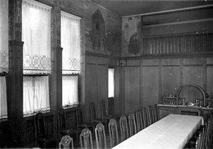 Часть столовой; на первом плане - художественные вышивки оконных занавесок.