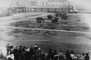 Верховая езда офицеров с дамами на плацу во время конных состязаний.