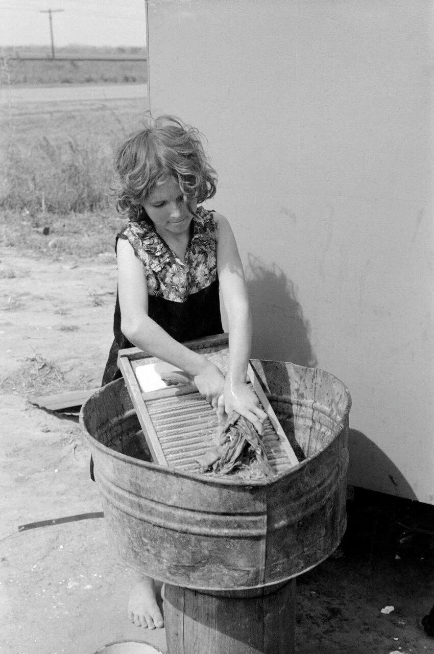 Двенадцатилетняя девушка, которая работает по дому в трейлере, пока ее три брата работают на полях возле Харлингена, Техас, 1939